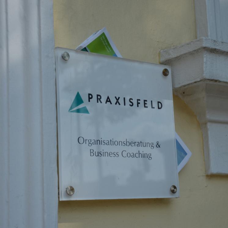 Türschild mit der Aufschrift PRAXISFELD Organisationsberatung Business Coaching
